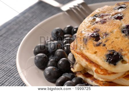 A Plate Of Pancakes With Fresh Blueberries