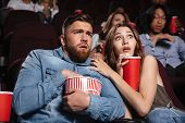 Young scared couple watching a horror movie while sitting at the cinema with popcorn poster