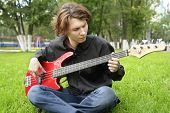 Teenage Boy Playing The Bass Guitar On The Lawn