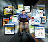 image of web surfing  - a business man is sitting on a black background and is working on a laptop computer - JPG