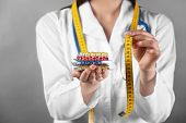 Doctor holding packs of pills and measuring tape in hands. Weight loss concept poster