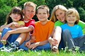 stock photo of happy kids  - A view of five happy kids sitting together and posing on the grass on a bright sunny day - JPG