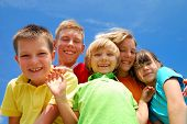 picture of happy kids  - A group of happy kids stand close together smiling as they pose under a clear blue sky - JPG