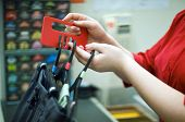 foto of shoplifting  - A female shop assistant at change room tags clothes for security - JPG