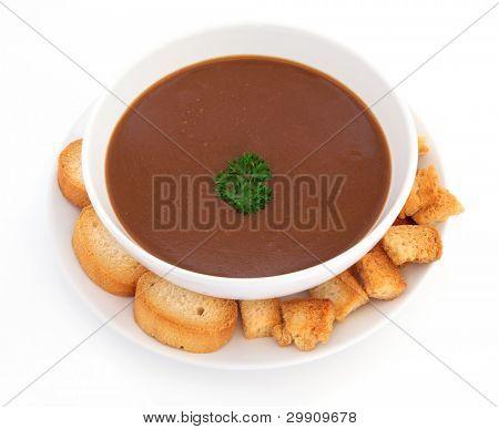 Sopa de rabo de boi com erva salsa e croutons torrados em uma tigela de porcelana com placa sobre backgro branco