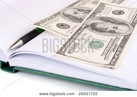 Two hundred-Dollars bills on the open notebook
