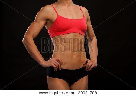 Female fitness bodybuilder posing against black background