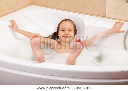 Child in the bathtub. Girl washes in the bathroom