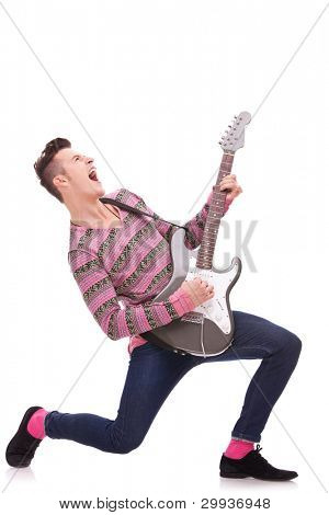 Rock star with a guitar screaming isolated over white background . rock and roll image of a young man playing an electric guitar and screaming. screaming young guitarist playing his guitar