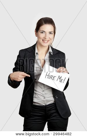 "Business woman holding a card board with the text message ""Hire me"""