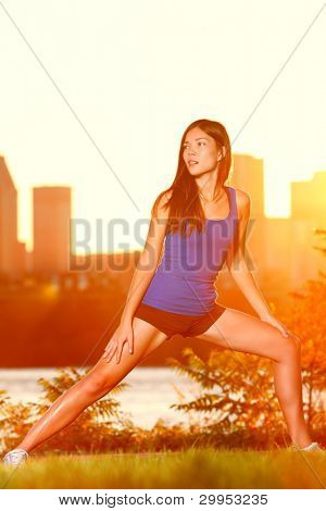 Runner woman training outside in city with skyline and sunset. Beautiful warm colors and gorgeous fit fitness model stretching after jogging workout in Montreal. Mixed race Asian Caucasian woman