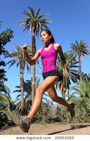 Woman running trail run at speed in tropical climate with palm trees. Beautiful multiracial Asian / Caucasian female fitness model training outdoors in summer for marathon race.
