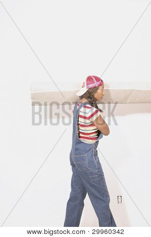 Side view of woman carrying rolled carpet
