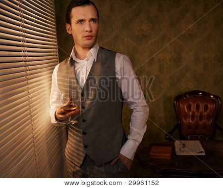 Retro man with a glass standing near window.