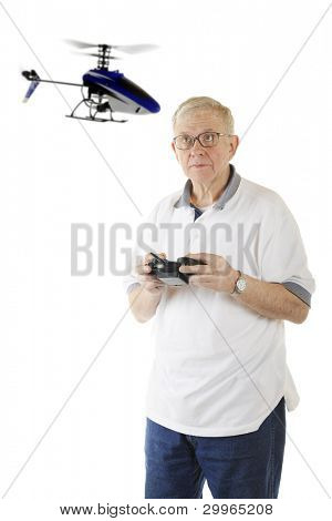 A senior man flying a remote controlled helicopter.  Focus on man.  Propellers with motion blur.  On a white background.