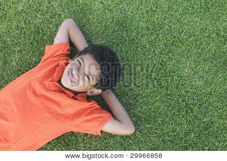 Retrato de niño tendido sobre la hierba