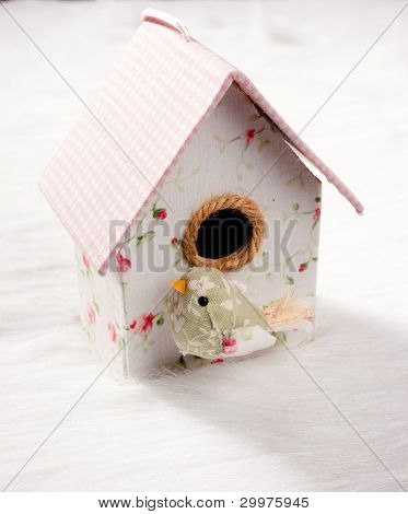 bird in a nest fabric house with round window in pastel colors