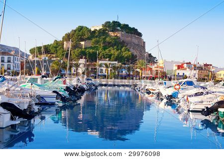 Denia mediterranean port village with castle mountain and blue sea water