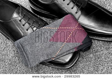 A pair of black leather dress shoes with argyle socks