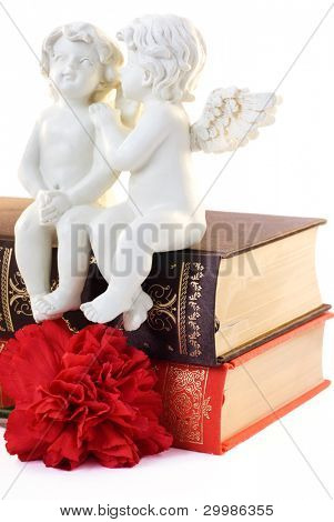 Figurine of two angels sitting on book