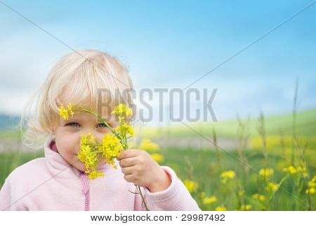 Little girl swelling yellow flowers in the field.