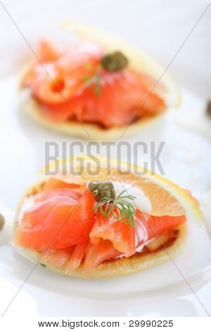 delicious appetizer with salmon pancakes , lemon and caper creme fraiche