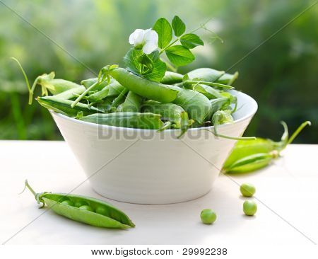 fresh peas in a white bowl on the table