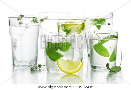 Glass of water and fresh herbs and edible flowers