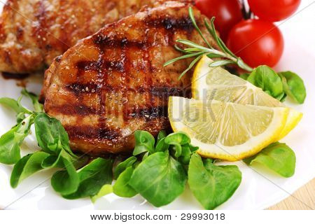 Closeup of grilled steak with lemon and rosemary