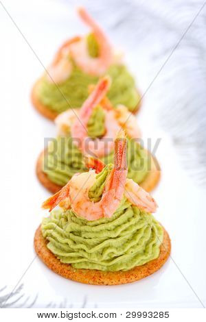 Avocado cream and prawns on crackers