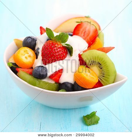 Fruity summer salad in white bowl with yogurt