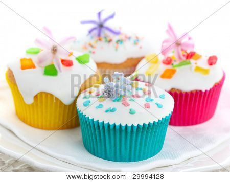 Easter cupcakes with spring flowers on white isolated background