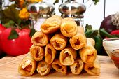 image of flauta  - Stack of chicken taquitos with hot sauce and sour cream in kitchen or restaurant - JPG