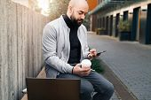 Man Sits On Bench And Uses Smartphone During Coffee Break,next Is Laptop.guy Checks Email On Mobile poster