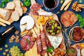 Italian Appetizers Or Antipasto Set With Gourmet Food On Kitchen Table Top View. Mixed Delicatessen  poster
