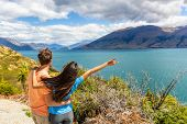 Travel couple enjoying wanderlust road trip in New Zealand, woman with arm up in excitement at Lake  poster