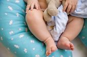 The Bare Feet Of A Cute One Year Old Baby Lying On A Special Pillow For Breastfeeding. A Toy In The  poster
