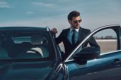 Luxury Style. Handsome Young Businessman Entering His Car While Standing Outdoors poster