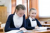 Children Write While Sitting At The School Desk. Hair Braided In Braids. Schoolgirl Girls Write In A poster