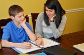 stock photo of tutor  - Tutor helping a young student with his studies - JPG