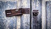 Vintage Rustic Stain Old Lock Stain U Line Hasp Hardened Staple Equipment On Painted Wooden Door. Ol poster