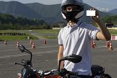 A Man Graduated From The Driving School, He Shows Driving Licence For Motorcycle. Driving Training.  poster