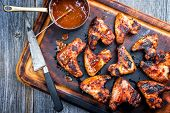 Traditional barbecue chicken wings with hot chili sauce as top view on a burnt cutting board  poster