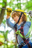 Cute Child In Climbing Safety Equipment In A Tree House Or In A Rope Park Climbs The Rope. Happy Lit poster