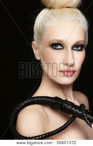 Young beautiful blond woman with braided bull whip in her hand