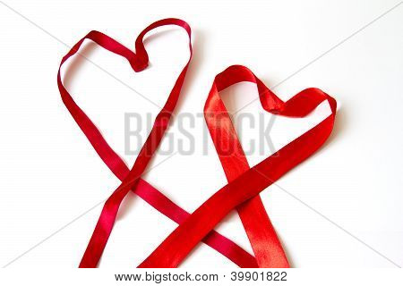 Two red bow hearts on white background