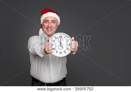 happy senior man in christmas hat showing the clock. studio shot over dark background