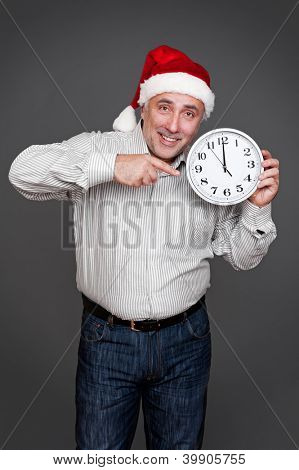 happy xmas man pointing at the clock and smiling. studio shot over grey background