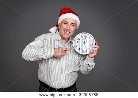 xmas man pointing at the clock and smiling. studio shot over dark background