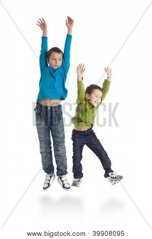 Two boys jumping on white background. Studio shot.